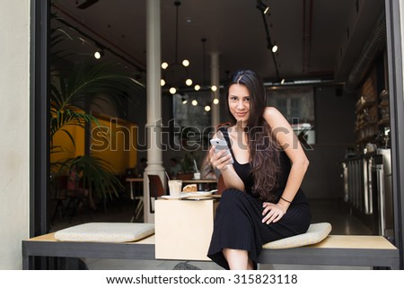 Charming woman holding her smart phone and look at the camera while sitting in modern coffee shop outdoors, beautiful female read good news on the cell telephone while resting in cafe after strolling - stock photo