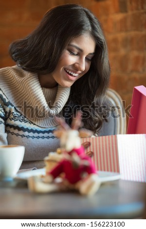 Charming woman in a restaurant opening gift from her couple, Christmas or Valentine's Day romantics - stock photo