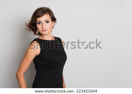 Charming woman in black dress on a gray wall. Woman 36 years old. - stock photo