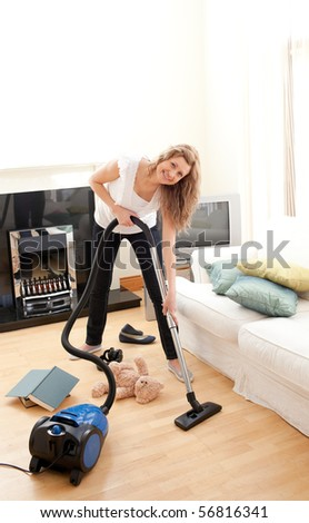 Charming woman in her chaotic living room with a vacuum cleaner
