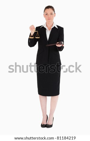 Charming woman in suit holding scales of justice and a gavel while standing against a white background - stock photo