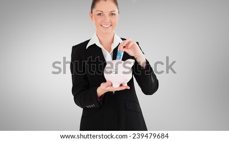 Charming woman in suit inserting a money bill in a pink piggy bank against grey vignette - stock photo