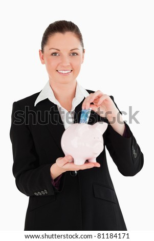 Charming woman in suit inserting a money bill in a pink piggy bank while standing against a white background - stock photo