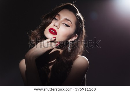 Charming woman looking at camera over dark background - stock photo