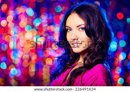 Charming woman looking at camera over sparkling background - stock photo