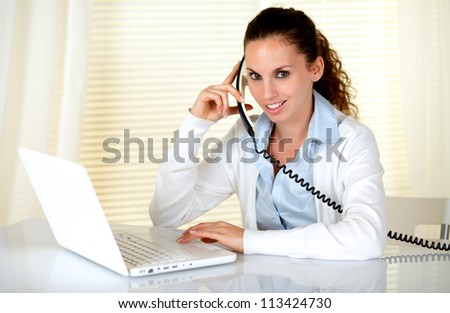 Charming woman looking at you while speaking on phone at workplace - stock photo