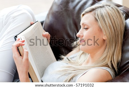 Charming woman reading a book sitting on a sofa in a living-room - stock photo