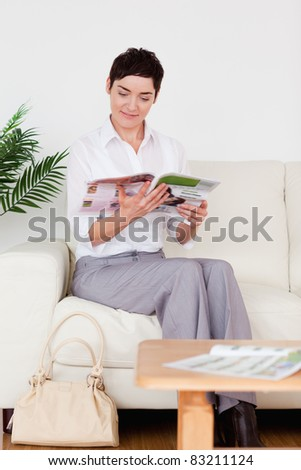 Charming woman reading a magazine in a waiting room - stock photo