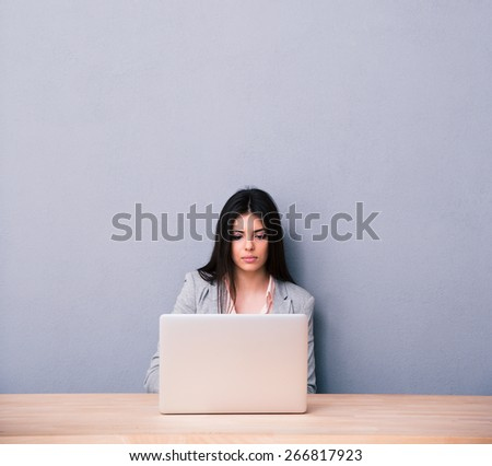 Charming woman sitting at the table and using laptop over gray background