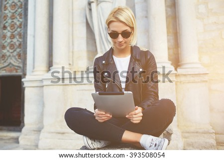 Charming woman wanderer is watching on touch pad photos that she took during excursion in museum. Hipster girl is watching video on web page via digital tablet, while is sitting against old building - stock photo