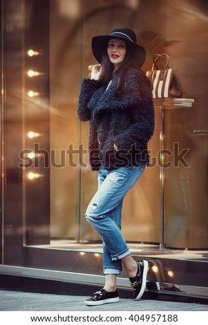 Charming woman with a beautiful smile after a walk to the shops posing in her new hat. Caucasian woman happy with the purchase of new things in a luxury clothing store - stock photo