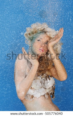charming woman with beautiful hair and snow on blue background