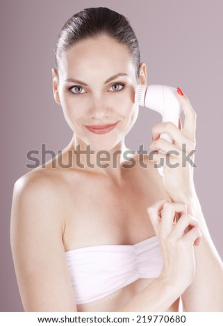 Charming woman with brush for deep cleansing facial. Skin care concept. High technology beauty. - stock photo