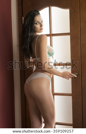 charming woman with perfect body posing in glamour indoor shoot in morning light with sexy lingerie and long hair, showing her ass and looking in camera