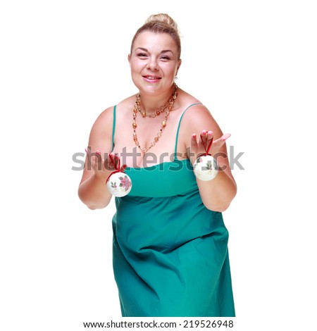 Charming women of average size in a beautiful blue dress is holding a Christmas ball on the Christmas tree on Holiday - stock photo