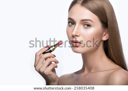 Charming young babe with lipstick and light makeup. Picture taken in the studio - stock photo
