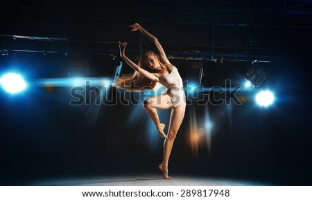 Charming young blonde ballet dancer posing on stage in theater - stock photo