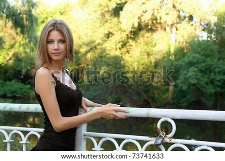 Charming young blonde in a park near the pond