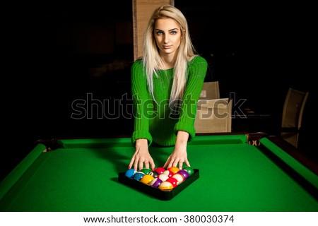 charming young blonde puts balls in triangle on pool table. Billiard sport concept. Pool billiard game. American pool billiard. - stock photo