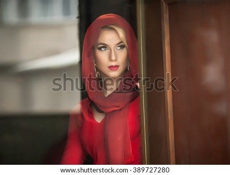 Charming young blonde with red blouse and headscarf posing in door frame. Sensual gorgeous young woman in red outfit opening the door for somebody.Portrait of attractive lady in red with romantic look - stock photo