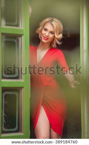 Charming young blonde with red dress posing in a green painted door frame. Sensual gorgeous young woman in red outfit with Marilyn Monroe look, opening the door for somebody, exposing her leg - stock photo