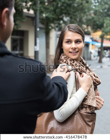 Charming young brunette flirting with guy at the street