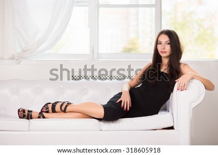Charming young brunette in black dress posing on the white sofa - stock photo