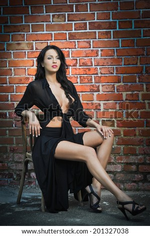 Charming young brunette woman in black and high heels near the brick wall. Sexy gorgeous young woman near old wall. Full length portrait of a provocative woman with long hair near a brick wall - stock photo