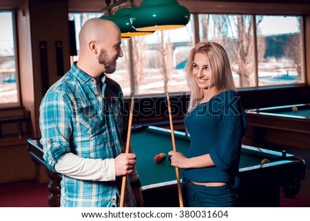 Charming young couple smiling at each others and plays billiard. Billiard sport concept. AMerican pool billiard. Pool billiard game. - stock photo