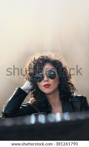 Charming young curly brunette woman with sunglasses and black leather jacket against wall. Sexy gorgeous young woman with modern look. Portrait of sensual girl with voluptuous mouth  - stock photo