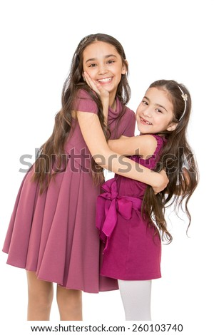 Charming young girl cheerfully embrace looking at the camera - isolated on white. - stock photo