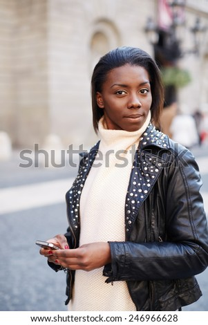 Charming young girl holding mobile phone standing on the square, attractive tourist girl on the walk in beautiful city, portrait of african young girl holding smart phone and looking to the camera - stock photo