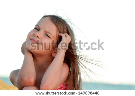 Charming young girl in a pink bathing suit sitting on a background of the sea/Girl on the Black Sea