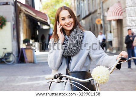 Charming young girl, wearing in gray jacket and scarf, with black bag, talking on the phone, with bike on the street of old European city, waist up - stock photo