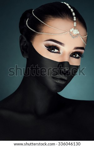 Charming young girl, with bright make-up, black paint on half of her face and tiara on her head, posing on the dark blue background, in studio, close up - stock photo
