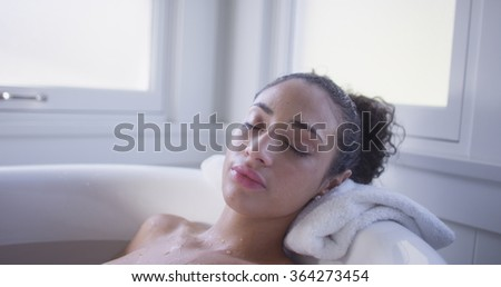 Charming young hispanic woman relaxed in a bathtub. - stock photo