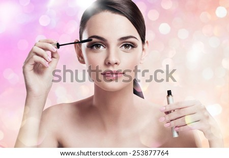 Charming young lady applying mascara / photoset of attractive brunette girl on blurred pink background with bokeh   - stock photo