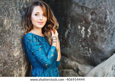 Charming young lady with blond-brown wavy hair, nice make-up and rose nails. Cute girl wearing blue dress. Model looking at camera. She standing near rock and holding her hair. Waist up, outdoor - stock photo
