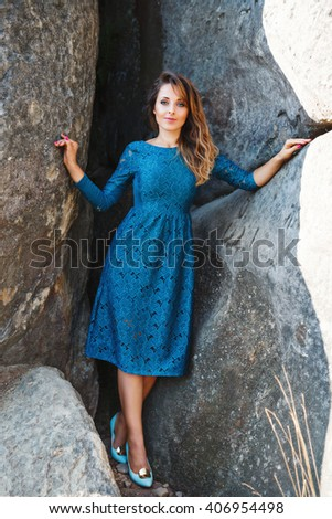 Charming young lady with blond-brown wavy hair, nice make-up and rose nails. Cute girl wearing blue dress and light blue shoes. Model smiling and looking at camera. Standing near rock. Full body - stock photo
