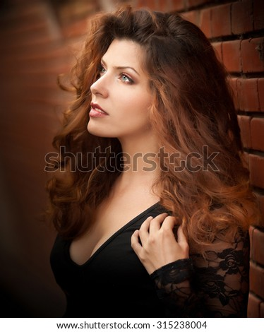 Charming young light brown hair brunette woman in black blouse near a red brick wall. Sexy gorgeous young woman with long curly hair near old wall. Beautiful portrait of a sensual woman with long hair - stock photo