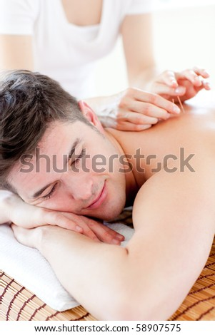 Charming young man in an acupuncture therapy - stock photo
