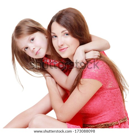 Charming young mother with his little daughter in a pink dress embracing and smiling isolated on white on a family theme - stock photo