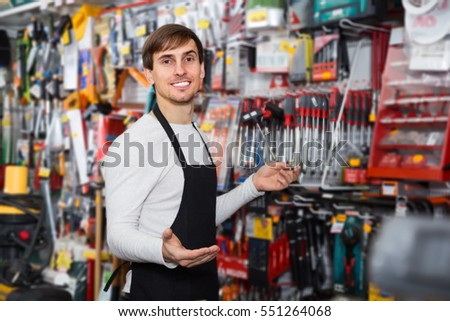 charming young salesman in apron with tools in supermarket