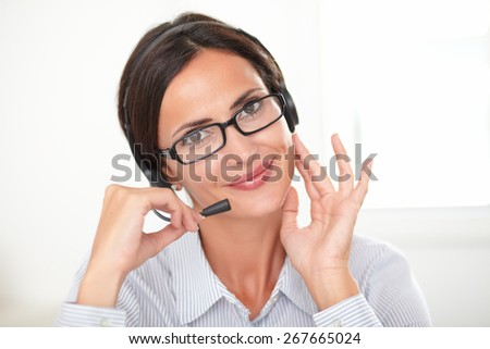 Charming young secretary in blue blouse speaking on headphones while cheerfully looking at you - stock photo