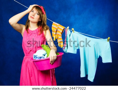 charming young tired housewife hanging clothes on clothesline using clothespin, against blue background