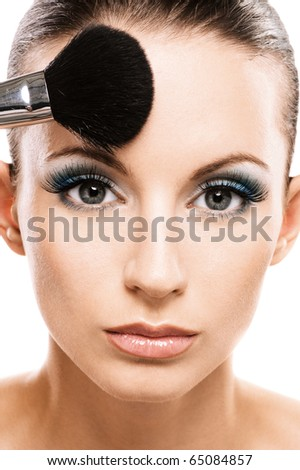 Charming young woman applying blusher close up. - stock photo