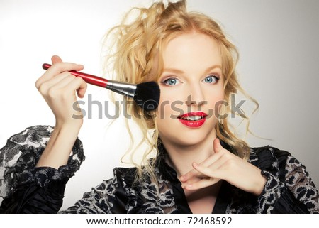 Charming young woman applying brush - stock photo