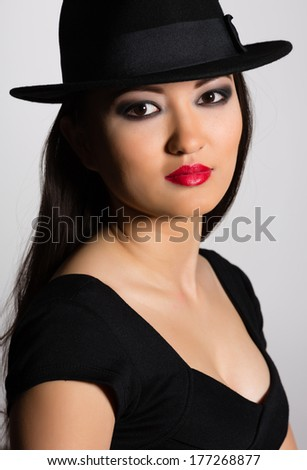 Charming young woman Asian in black hat on gray background.