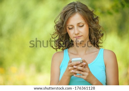 Charming young woman close-up in blue shirt reads message to mobile phone, against green of summer park. - stock photo