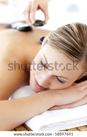 Charming young woman enjoying a back massage with hot stone in a spa center - stock photo